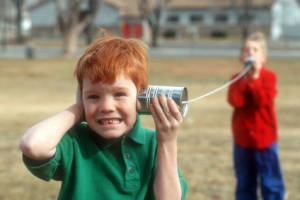 children playing with tin can & string telephone